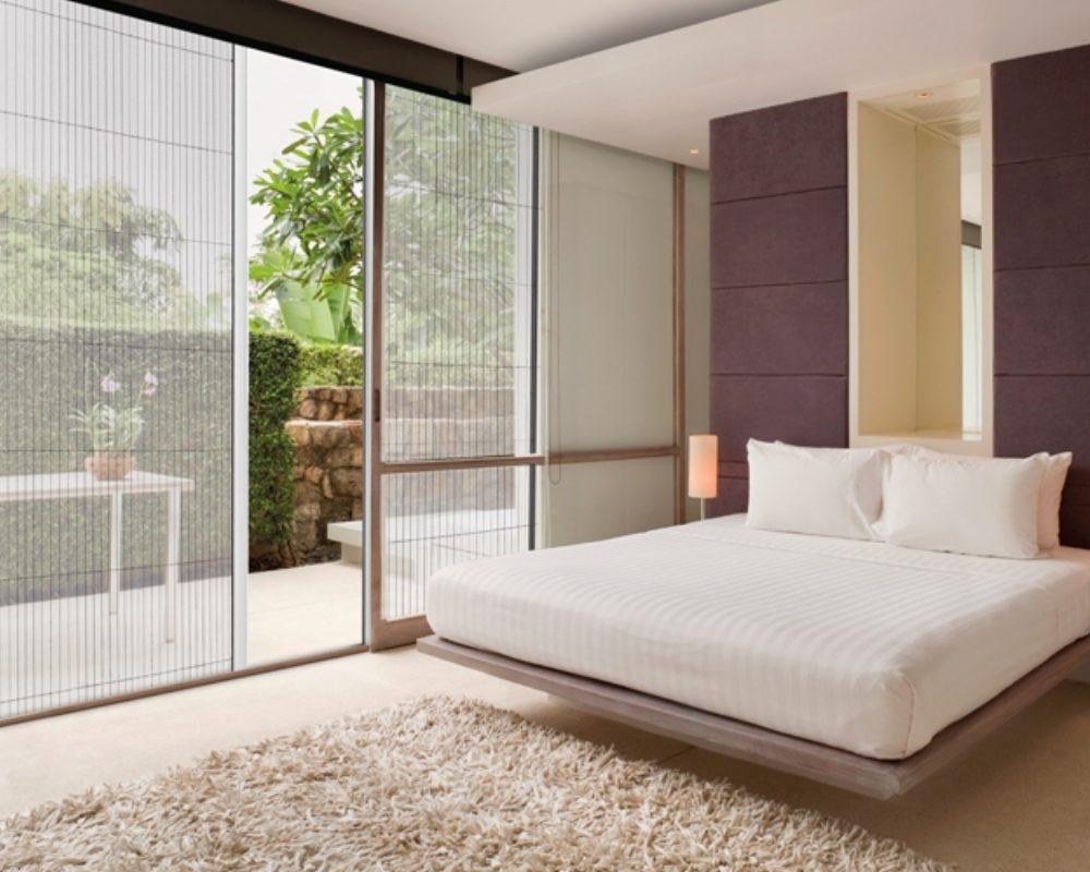 Ein große Schiebetüre mit verbautem Insektenschutz der Firma Reflexa in einem Schlafzimmer
