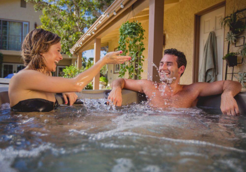 Ein Paar genießt die Massage in einem Outdoorwhirlpool der Marke Hotspring